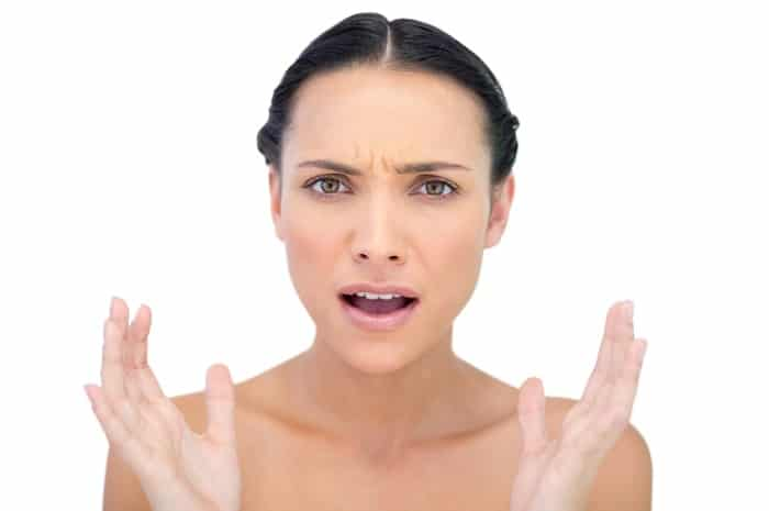 a young woman with healthy skin looking angry
