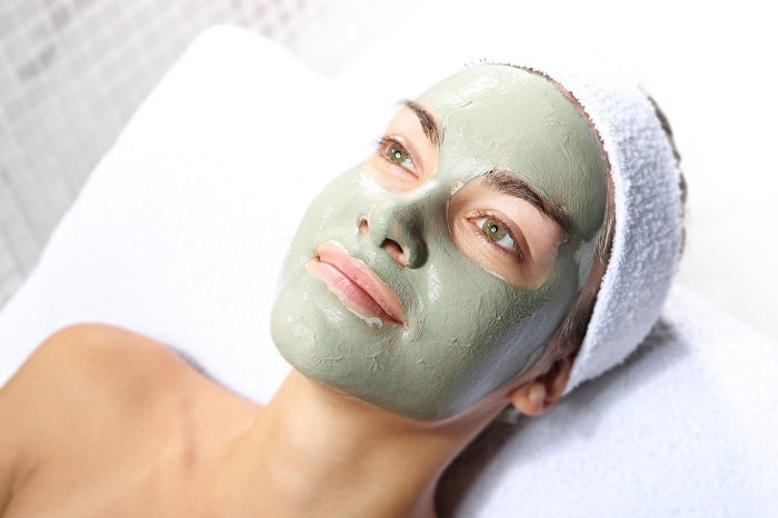 a woman with a green acne mask