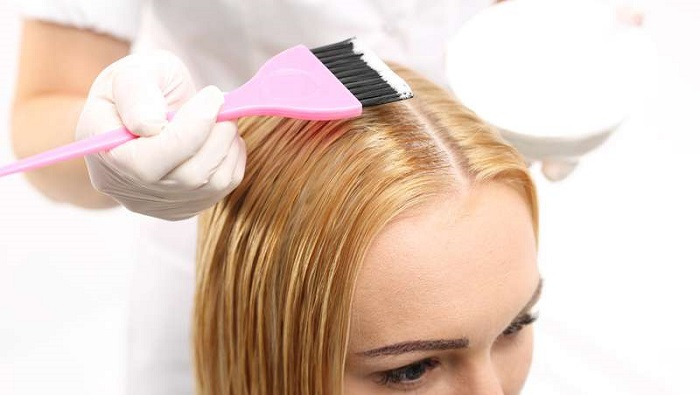 a dye brush on a young woman's hair