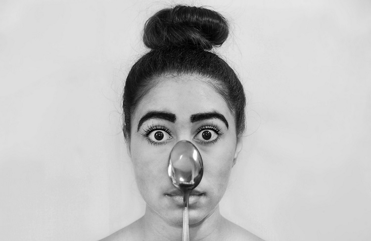 a girl with a spoon on her face