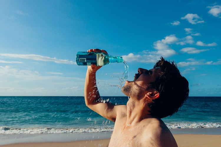 a man drinking water from a bottle