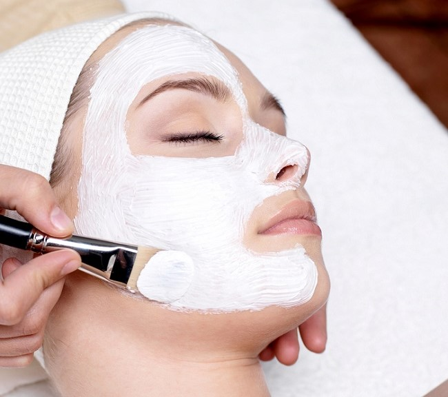 applying a face cream on a woman's face
