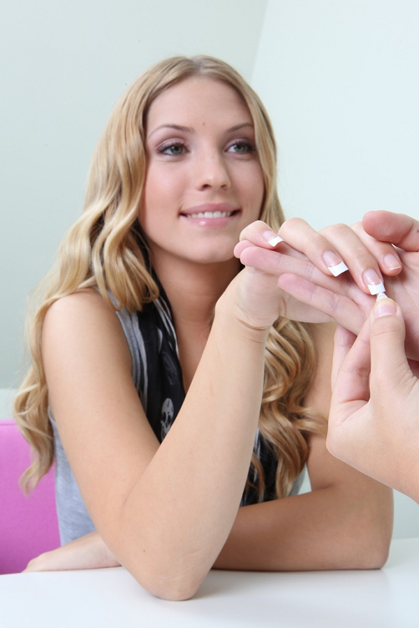 a cosmetician doing a woman's manicure