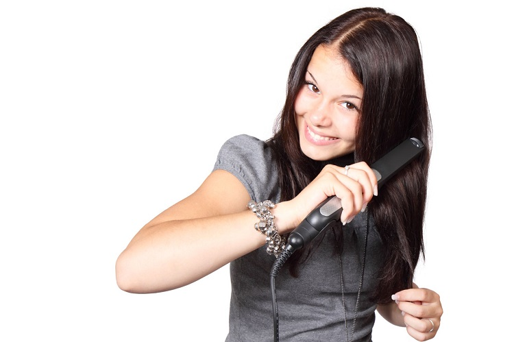 a woman with straight hair using a flat iron