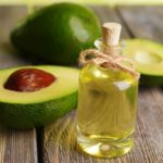 a sliced avocado fruit and a bottle of oil