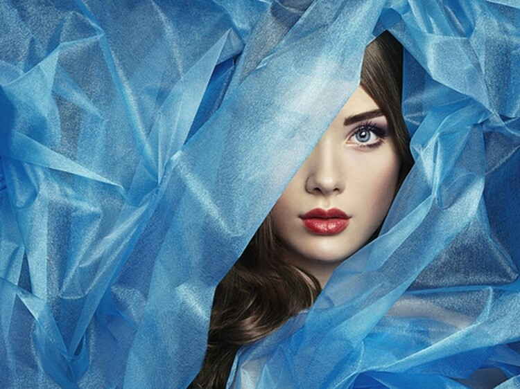 a young woman covered with a blue veil