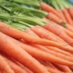 a pile of carrots on a market table