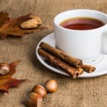 a white cup of tea with nuts and cinnamon sticks