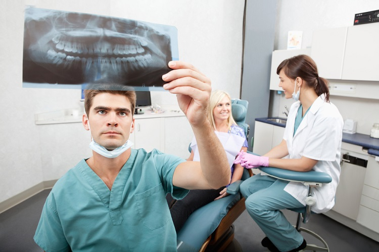 a dentist in his office looking at an oral X-Ray
