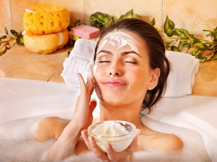 a woman in the bathtub applying a face mask