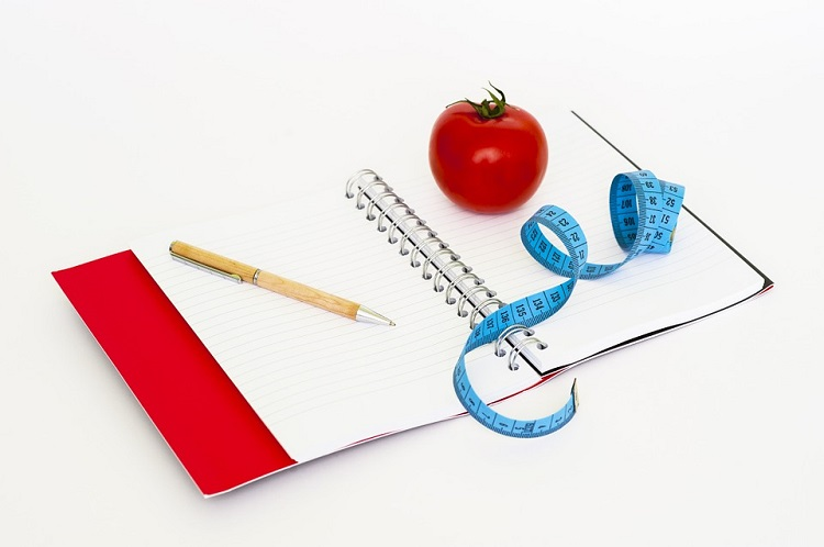 a tomato and a measurement tape on a notebook