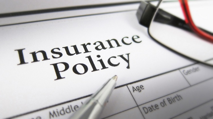 an insurance policy with a pen and some glasses on it