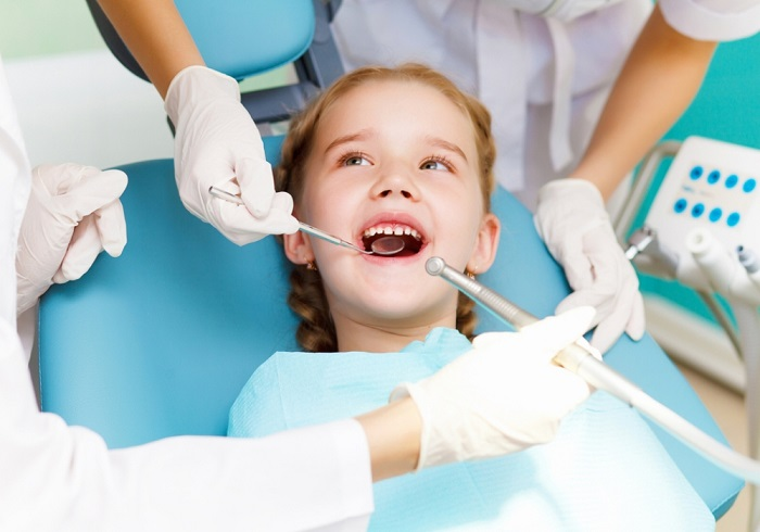 a little girl on a dentist chair