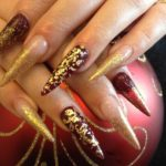 a woman's hands wearing a golden glittery manicure