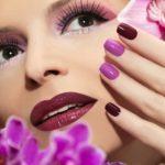 a woman with beautiful makeup and purple nail polish