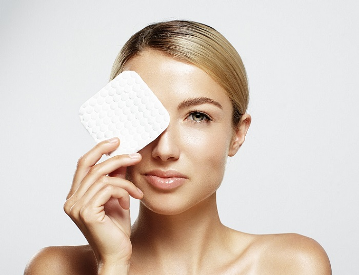 a young woman removing her eye makeup with a pad