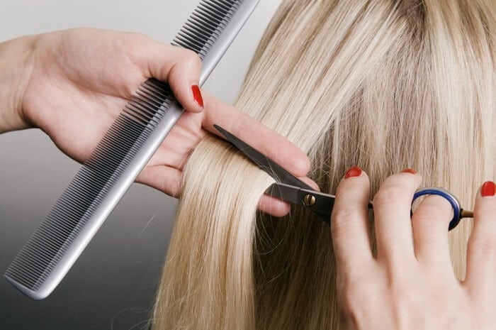 a woman with blonde hair having her locks trimmed
