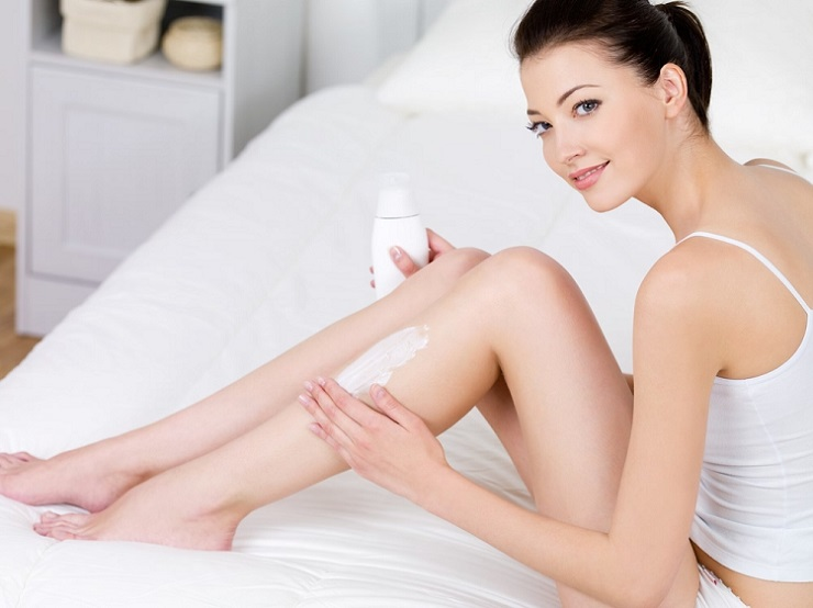 a woman applying a skin firming lotion on her legs