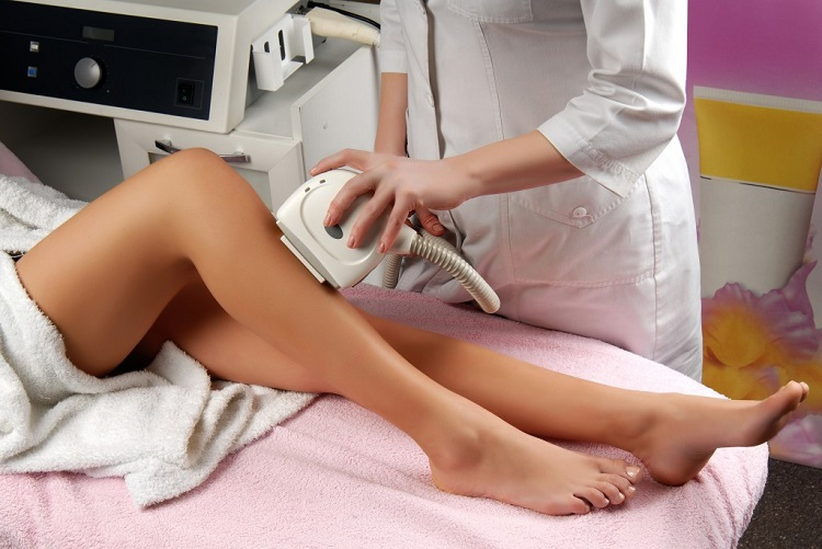 a beautician applying a laser hair removal treatment to a female client