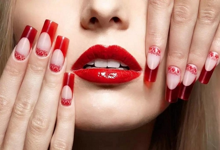 a woman with red lipstick holding her hands on her face