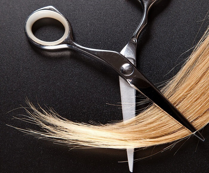 a pair of scissors and a blond lock