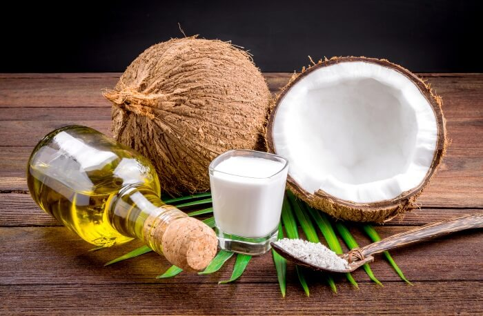 coconut oil and milk next to a real coconut