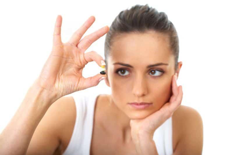 Woman Looking at Pills
