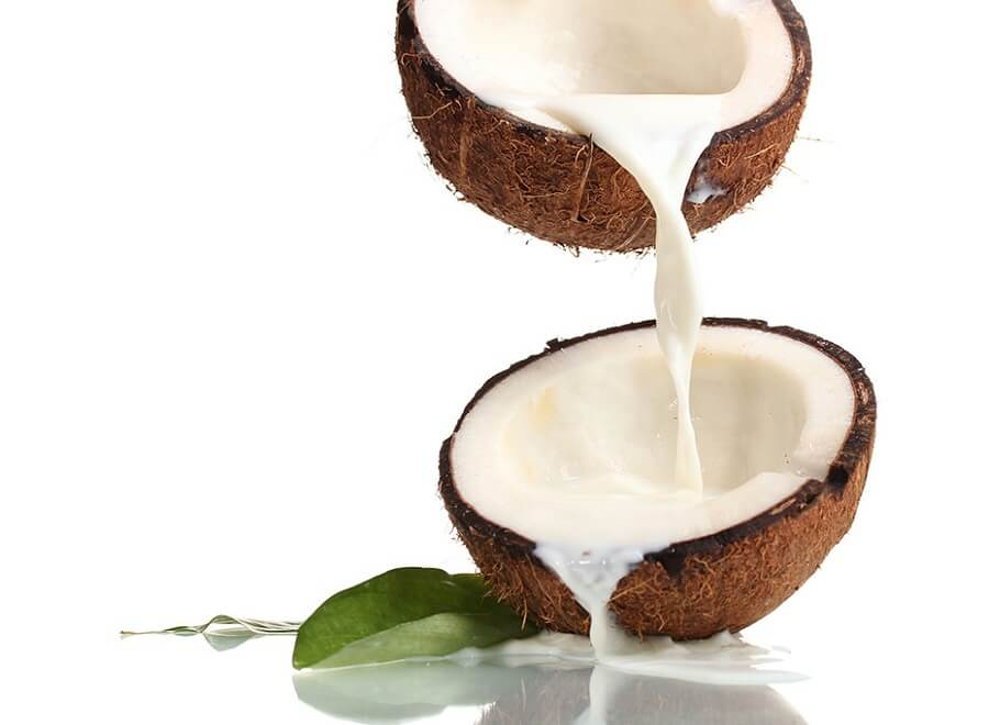 pouring milk from one half of a coconut into another half