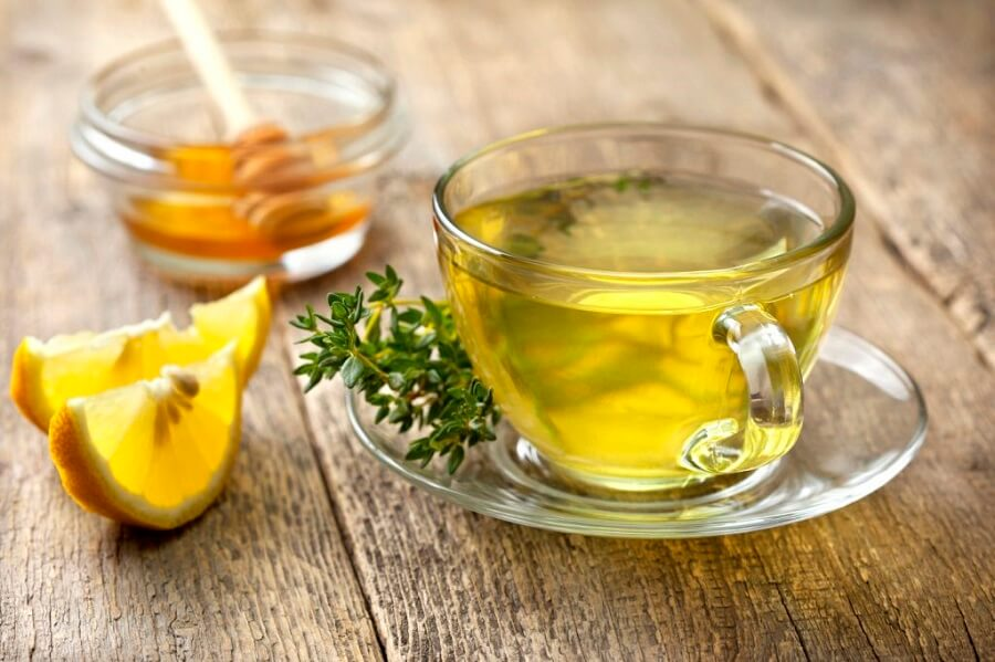 a cup of thyme tea next to some honey and slices of lemon