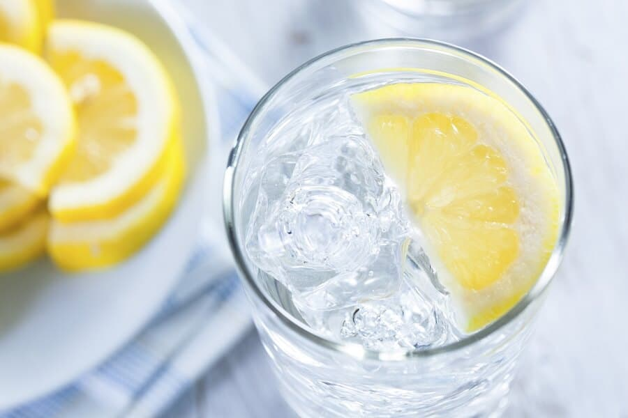 glass of water with a slice of lemon in it