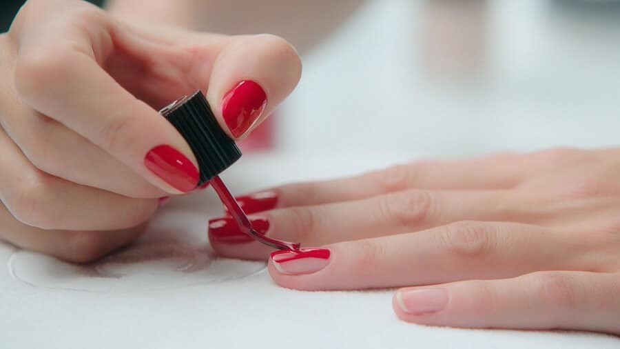 woman painting her nails red