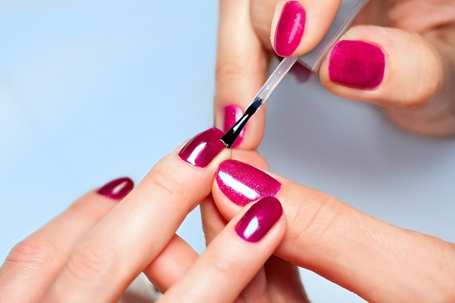 woman putting nail polish on her nails