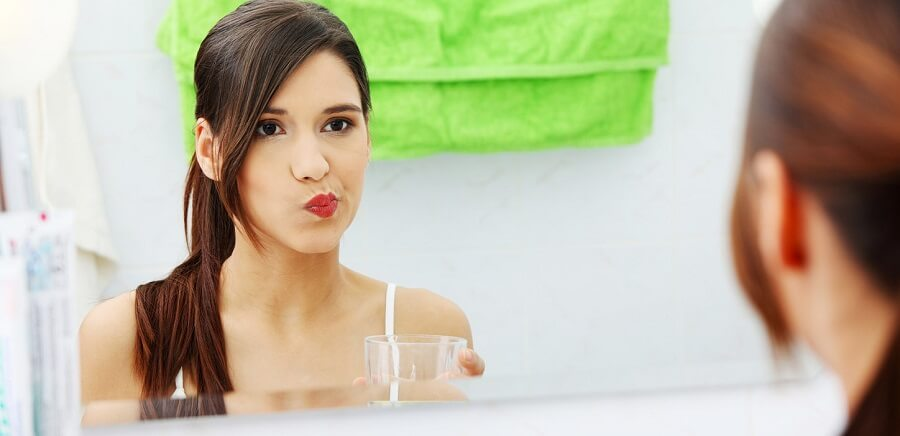woman looking in the mirror and using mouthwash