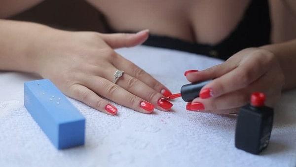 Applying red nail polish