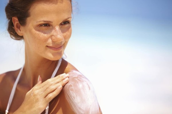 Woman applying lotion on shoulder