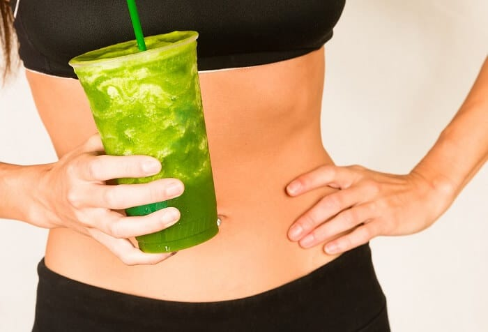 slender woman with green smoothie
