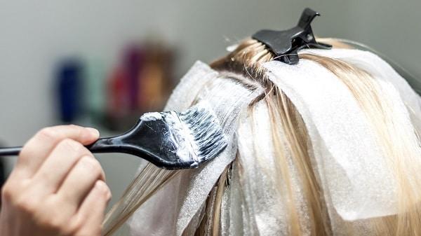 Blonde woman applying hair dye on her hair