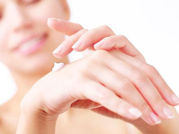 A woman putting white cream on her right hand
