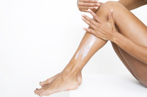 Woman applying white lotion on legs