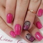 Pink nails with black pattern on the ring finger