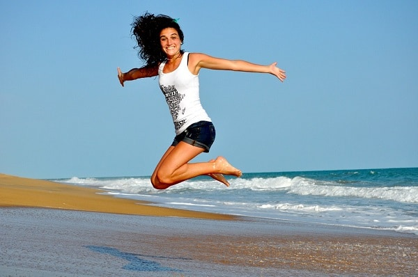 smiling girl jumping on beach