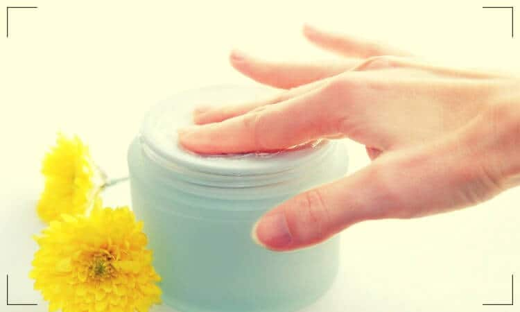 Woman placing two fingers into a moisturizing cream jar