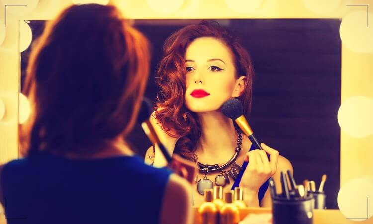 Woman looking in the mirror and applying makeup