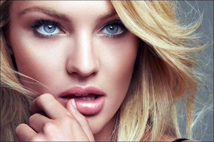 Close up of Candice Swanepoel holding her hand to her mouth
