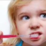 Close up of a blonde girl brushing her teeth with a half red, half transparent toothbrush