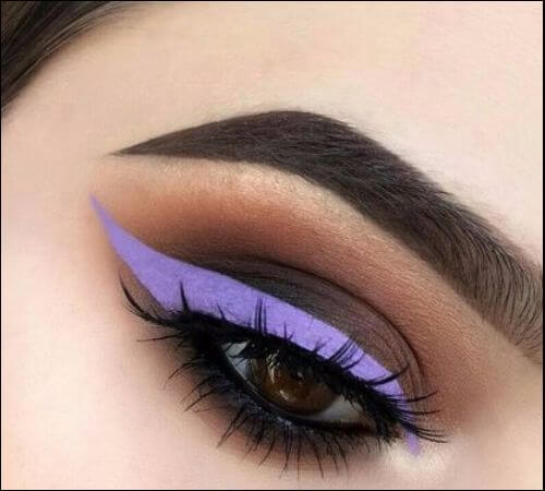 Close up of a girl's right eye with heavy makeup and purple eyeliner