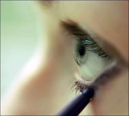 Side shot of a girl with blue eyes applying eyeliner with a dull pencil