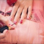 Girl doing her own nails with red polish, on pink backgrounds