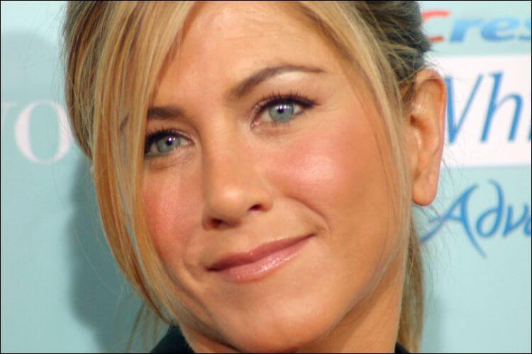 Close up of Jennifer Aniston's face, slightly smiling, with her blonde hair framing her face