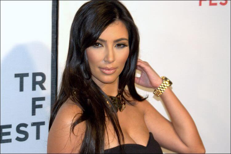 Photo of Kim Kardashian West, dressed in a black dress, wearing a black necklace and a gold watch